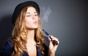 Elegant woman smoking e-cigarette with smoke wearing suit